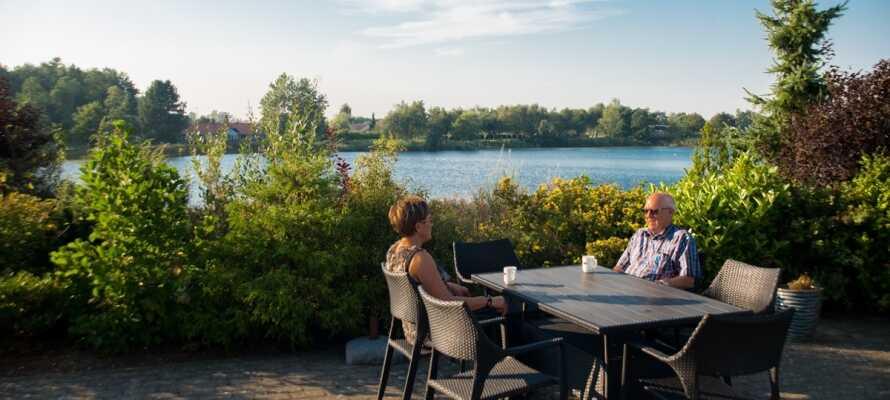 Rum med utsikt över gårdsplanen eller mot Aabybro-sjö och naturområdet.