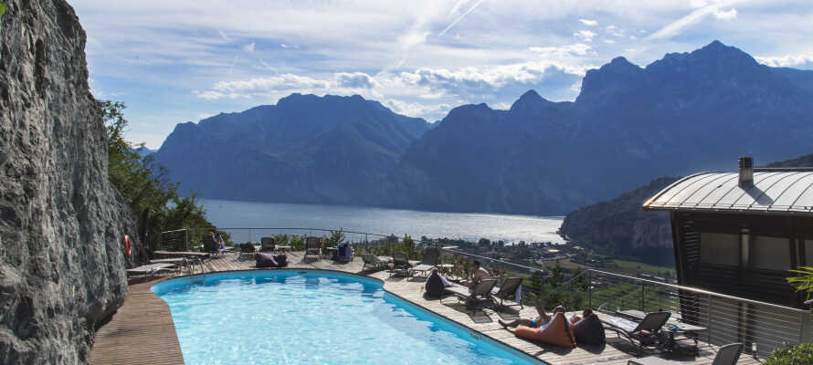 Platz zum Sonnenbaden auf den Sonnenliegen am Pool - mit Blick auf Berge und See.