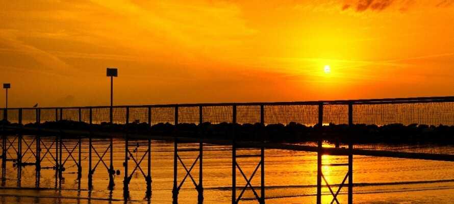 Gör mysiga kvällspromenader och njut av den fantastiska solnedgången vid stranden i Rimini.