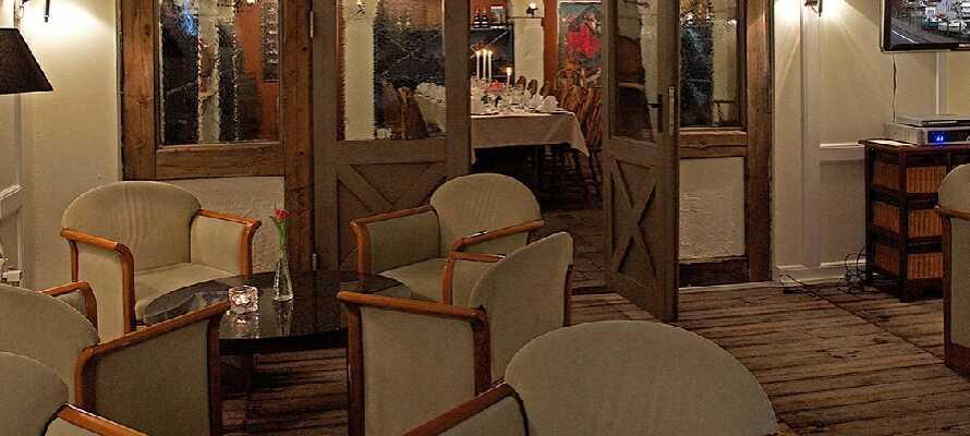 Hotellets opholdsstue, komplet med bløde møbler og TV, indbyder til hyggelige og afslappende stunder.