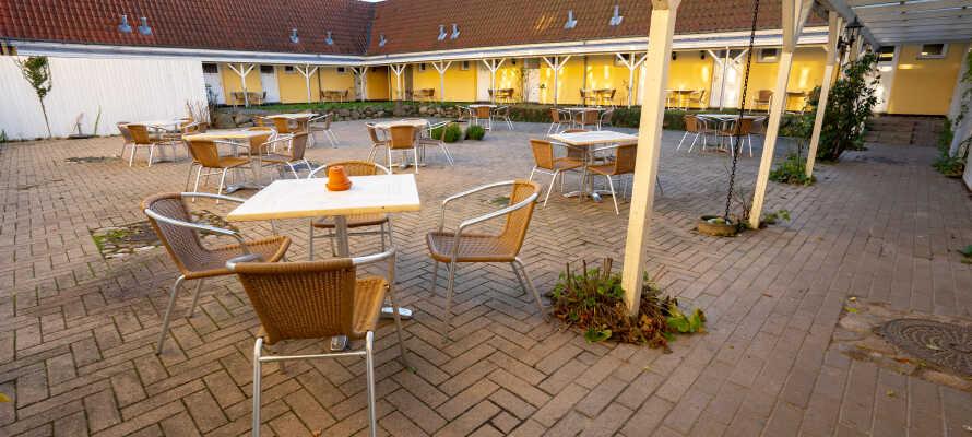 I hotellets hyggelige gårdhave kan I nyde en kop kaffe i det gode vejr