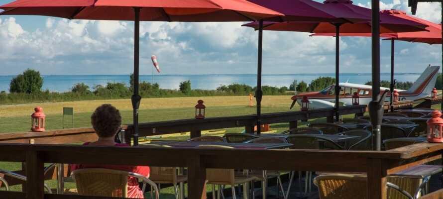 Fra kroens terrasse kan I se havet og den omkringliggende natur, mens I nyder en forfriskning!