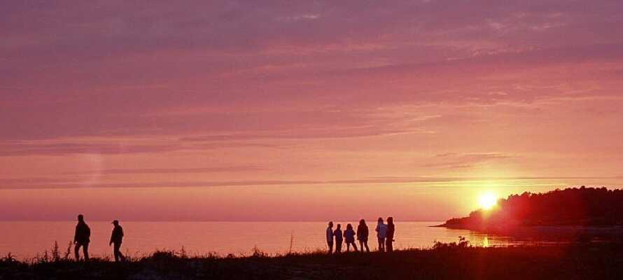 Gå en tur på øyen, merk stemningen i havnen og nyt den vakre solnedgangen ved havet.