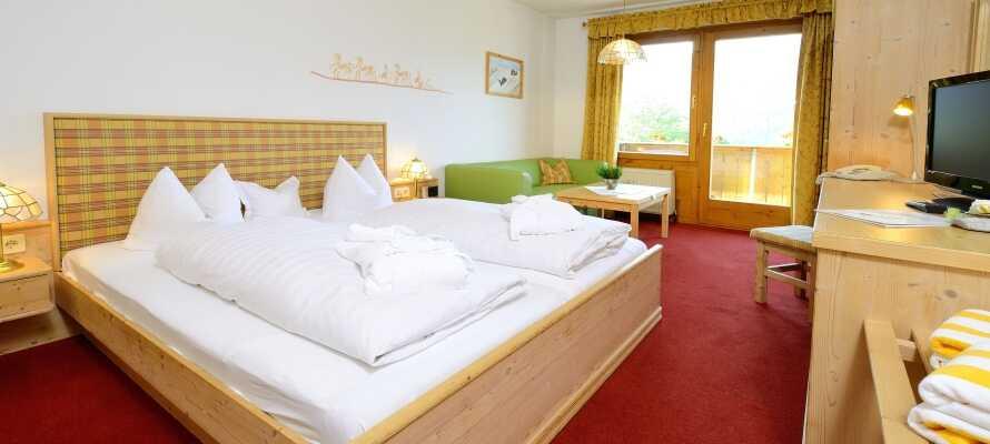 Die Zimmer sind gemütlich mit Holzmöbeln eingerichtet und verfügen jeweils über einen Balkon mit Berg- oder Gartenblick.