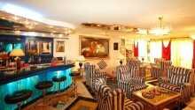 Rummen är inredda i varma färger och värdeskåp, TV och minibar.