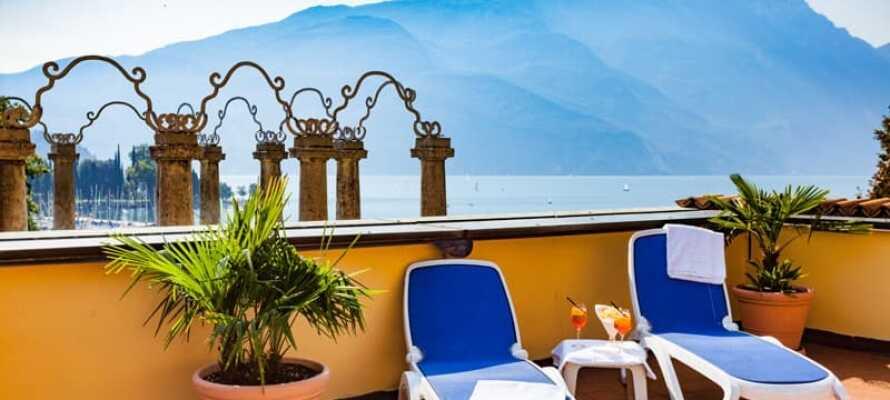 På hotellets takterrasse kan dere nyte en drink i solen og den flotte utsikten over Gardasjøen