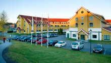 Hotellets façade med parkeringspladsen.