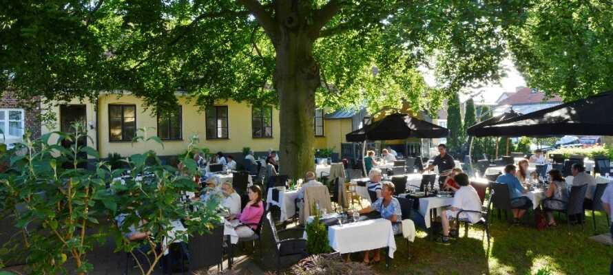 Om sommeren kan I spise i hotellets dejlige have under det enorme grønne træ.