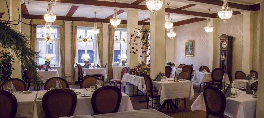 Nyt tradisjonelle danske måltider i den stemningsfule restauranten, som preges av lysekroner og varme farger.