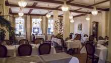Den lyse restauranten er innredet i en klassisk stil med varme farger og vakre krystallysekroner, som gir en herlig stemning.