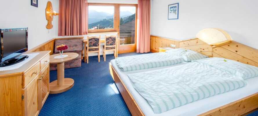 Hotellets værelser er indrettet i tradionel tyrolerstil, alle med balkon og idyllisk natur lige udenfor vinduerne.