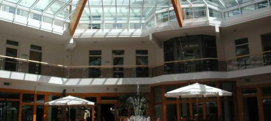 Nyd en drink, en kaffe eller blot en stille stund i hotellets store indendørs atriumgård.