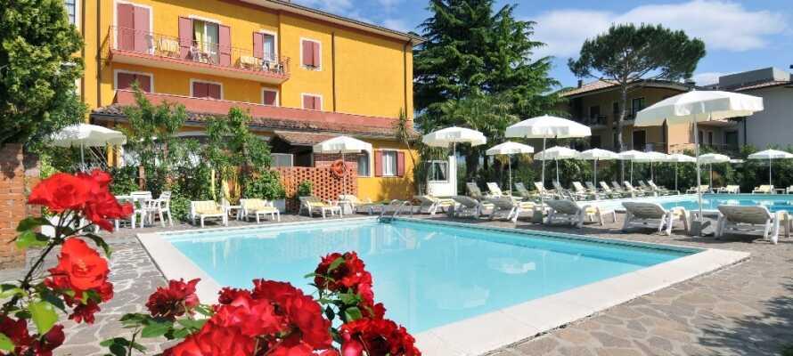 Nyd livet og det dejlige vejr ved hotellets poolområde med to udendørs swimming pools; én til voksne og én til børn.