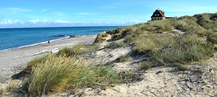 Promenera på stranden och få vind i håret och sol i ansiktet medan ni njuter av havets svallande vågor
