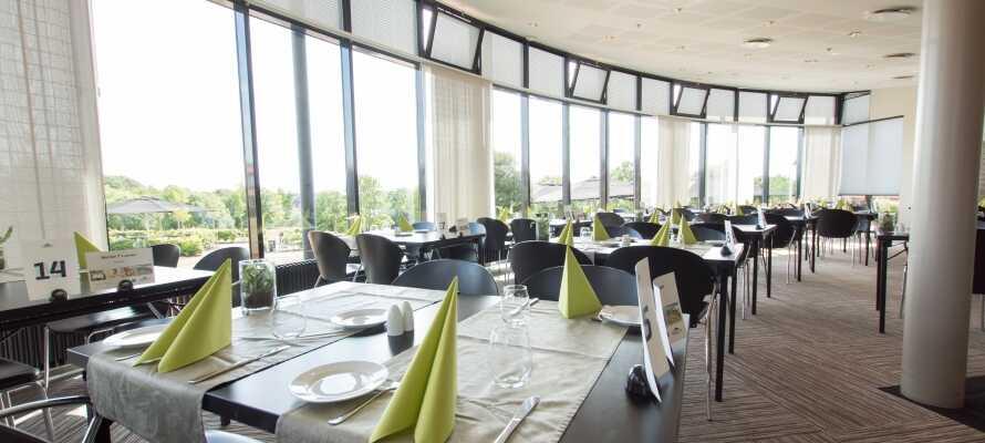 Hotellets ljusa restaurang erbjuder en vacker utsikt över trädgården och vattnet.