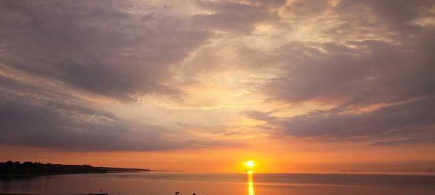 Ta en trevlig kvällspromenad vid vattnet och njut av den vackra solnedgången