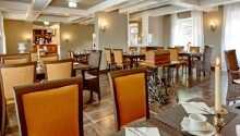 Njut av en god frukost i hotellets restaurang som är inredd med fina antika möbler.
