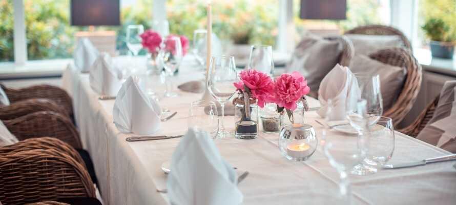 Njut av atmosfären medan ni äter middag i den trevliga och ljusa restaurangen
