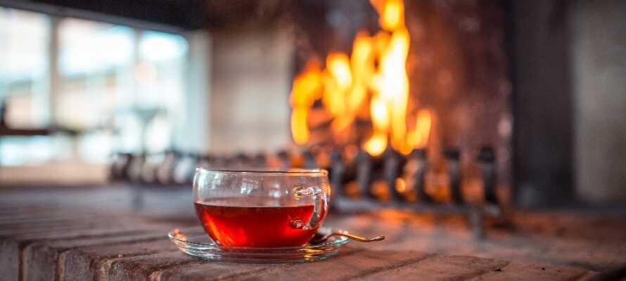 Njur en kopp te framför öppna spisen, medan ni kopplar av och laddar för nya upplevelser