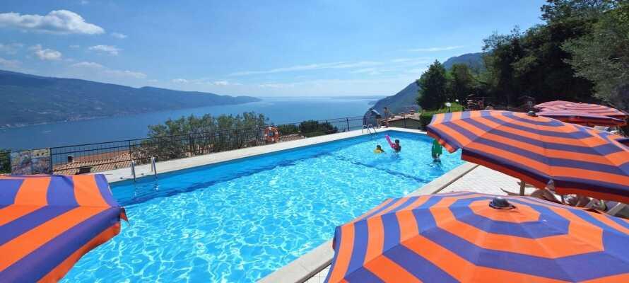 Koppla av vid hotellets poolområde med två utomhuspooler, solstolar, parasoller och en helt strålande utsikt.