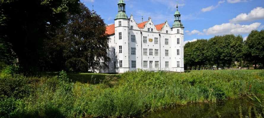 Das schöne weiße Renaissance-Schloss Ahrensburg. Es liegt mitten im grünen Schlosspark - auf der kleinen Insel inmitten eines Sees.