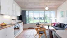 I bor I nydelige feriehuse, som er indrettet med køkken og stue.