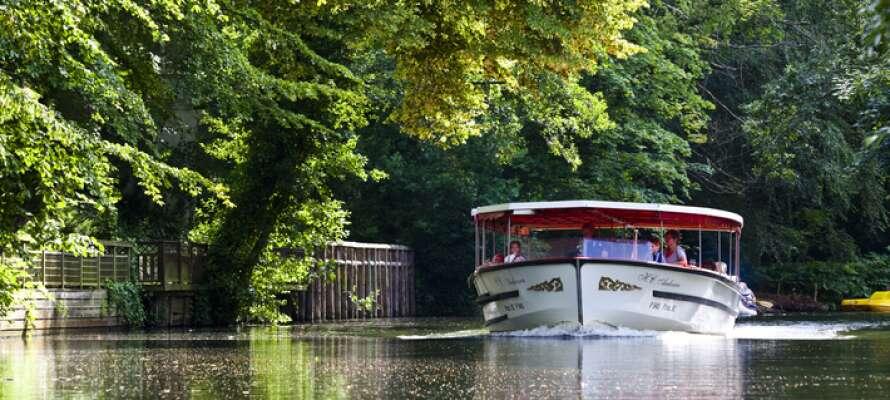 Reis på en fantastisk tur med Odense Å-båt, som seiler forbi byens prisbelønte Zoo.