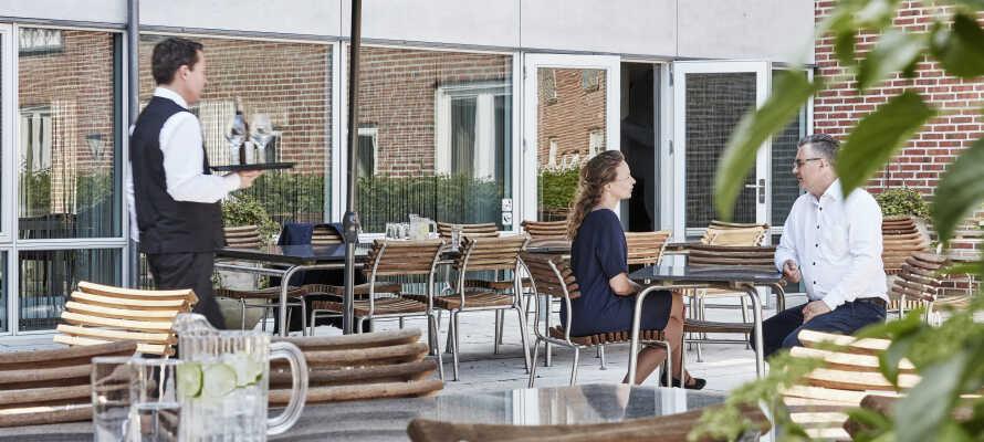 Genießen Sie das ruhige Urlaubsleben mit einem Gespräch und einer Erfrischung auf der großen Hotelterrasse.