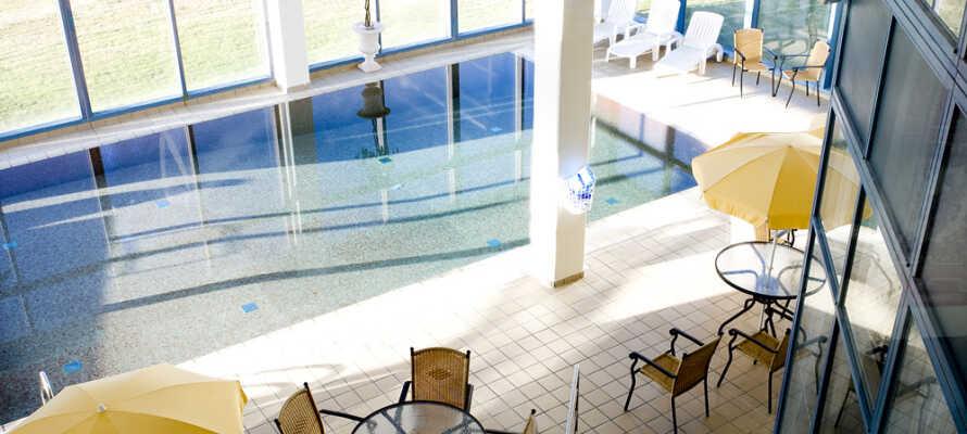 Ta en dukkert i hotellets innendørsbasseng. Det ligger i et oppvarmet anlegg med tropisk atmosfære.