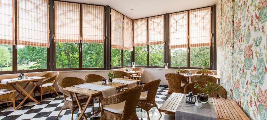 Nyd en dejlig kop kaffe i hotellets havestue med udsigt til den smukke slotspark.