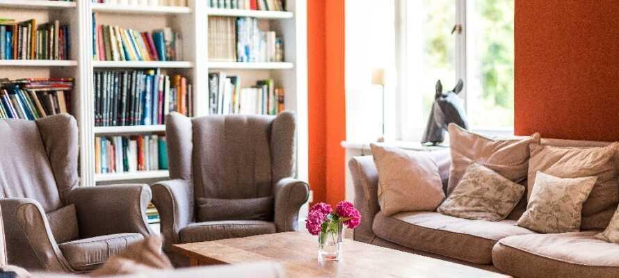 Slap af med en god bog eller en avis i hotellets kombinerede bibliotek og opholdsområde.