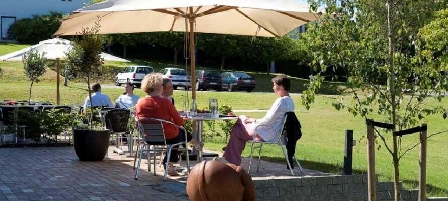 I godt vejr kan gæsterne nyde livet og de grønne omgivelser på hotellets store terrasse.