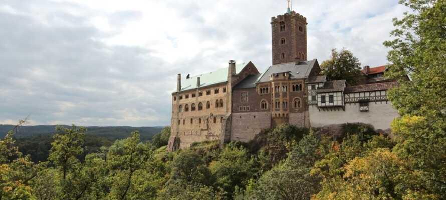 Besøk Middelalderborgen Wartburg, som troner på imponerende vis over den hyggelige byen Eisenach.