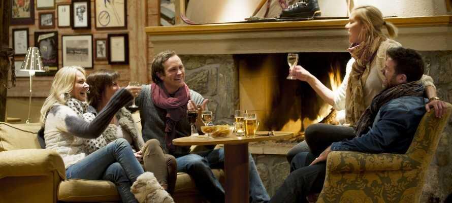 Nyd et glas vin eller en drink foran pejsen i godt selskab efter en begivenhedsrig dag i sneen