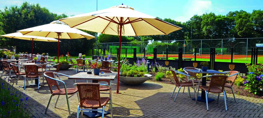 Tilbring ettermiddagen på terrassen med utsikt til hotellets tennisbaner