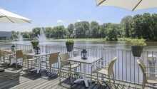 Njut av en drink på hotellets terrass med utsikt över parken och dammen.