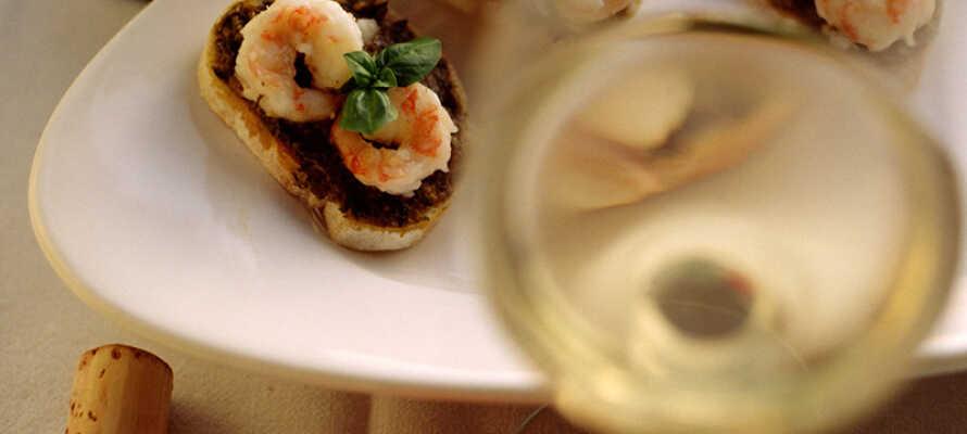 Nyt en god middag i hotellets restaurant med litt vin for å høyne opplevelsen.