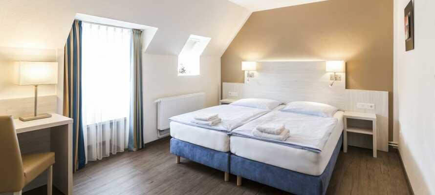 Vælg mellem hotellets rummelige værelser eller  de hyggelige ferielejligheder.