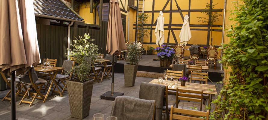 Hotellets gårdhave fungerer som en eftertragtet oase i sommerhalvåret. Her kan livet nydes med drinks, øl, vin og dejlig stemning.