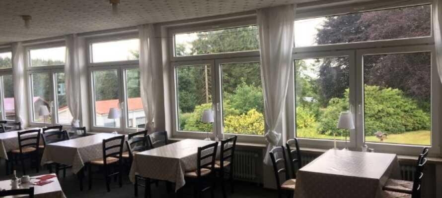 Morgens stärken Sie sich im hellen Hotelrestaurant mit Blick auf den Garten mit einem schönen Frühstück.