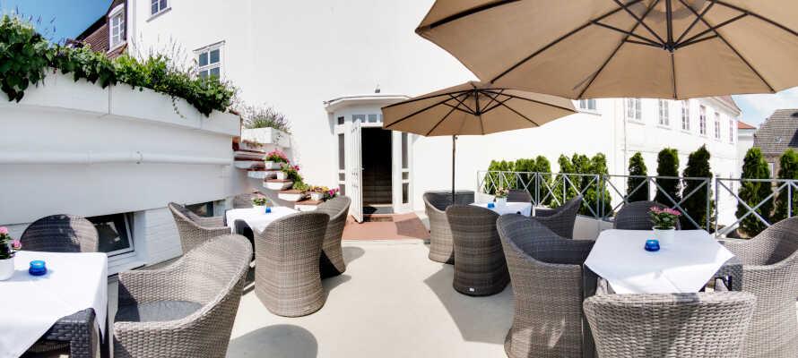 Nyd solen og roen på hotellets dejlige terrasse efter en oplevelsesrig dag.