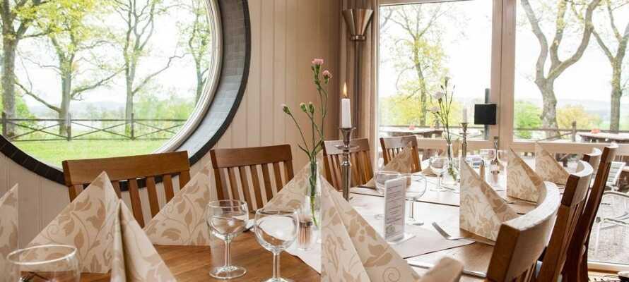 Spis middag i hotellets lyse restaurant med utsikt til parken