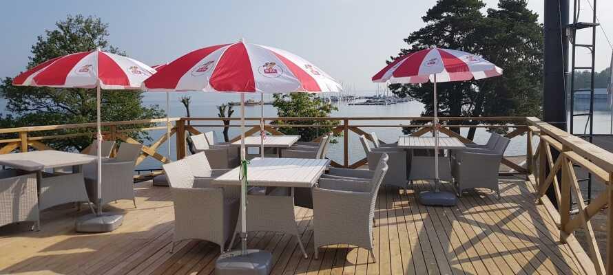 Hotel Wettern ligger ligger langs med stranden ved Vättern. Det er en nydelig utsikt med stoler utenfor på terrassen.