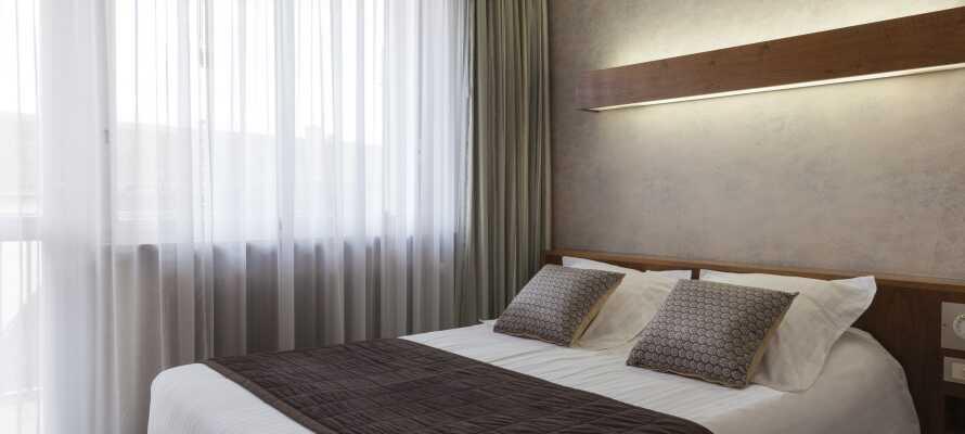 Hotellets flotte og komfortable værelser er indrettet i bløde farver med træpaneler og stilfulde møbler.