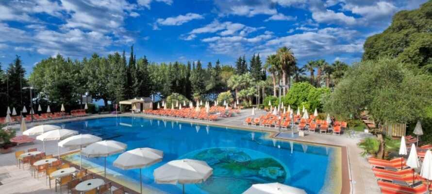 Hotellet har et innbydende utendørs svømmebasseng med liggestoler og parasoller
