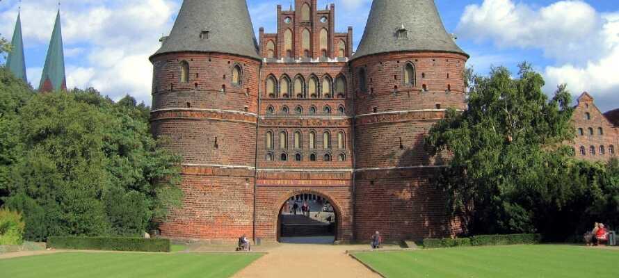 Besøg Holstentor og gå ind i byen gennem den gamle byport. I kan vælge at gå rundt selv eller betale for en guidet tur.