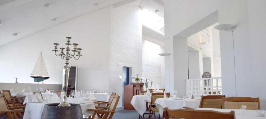 Spis middag og nyd et godt glas vin til maden i hotellets lyse restaurant.