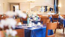 Börja morgonen med frukost som serveras i hotellets ljusa omgivningar