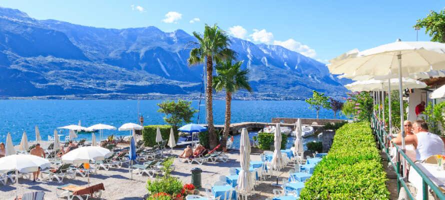 Det tar kun få minutter ned til Gardasjøen, hvor hotellet har en privat strand med solsenger og parasoller.