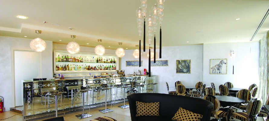 Njut av en drink eller espresso i den luftiga inomhusbaren.